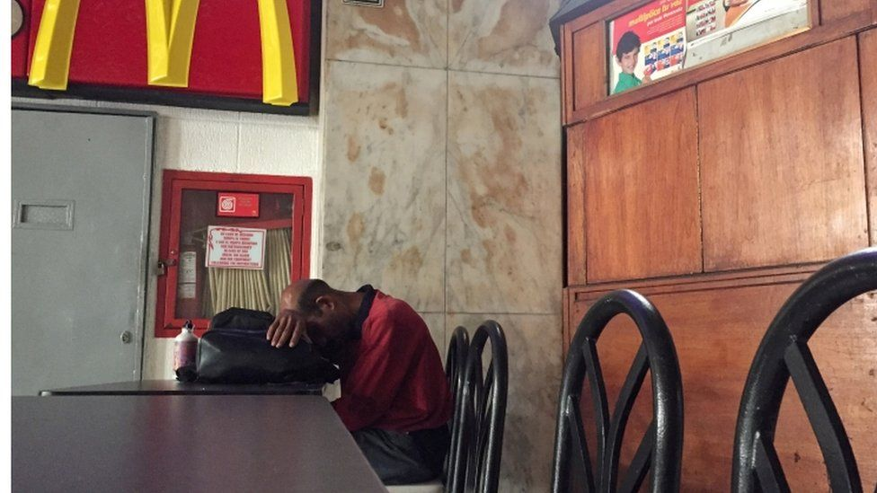 A man rests in a closed down restaurant during the power cut