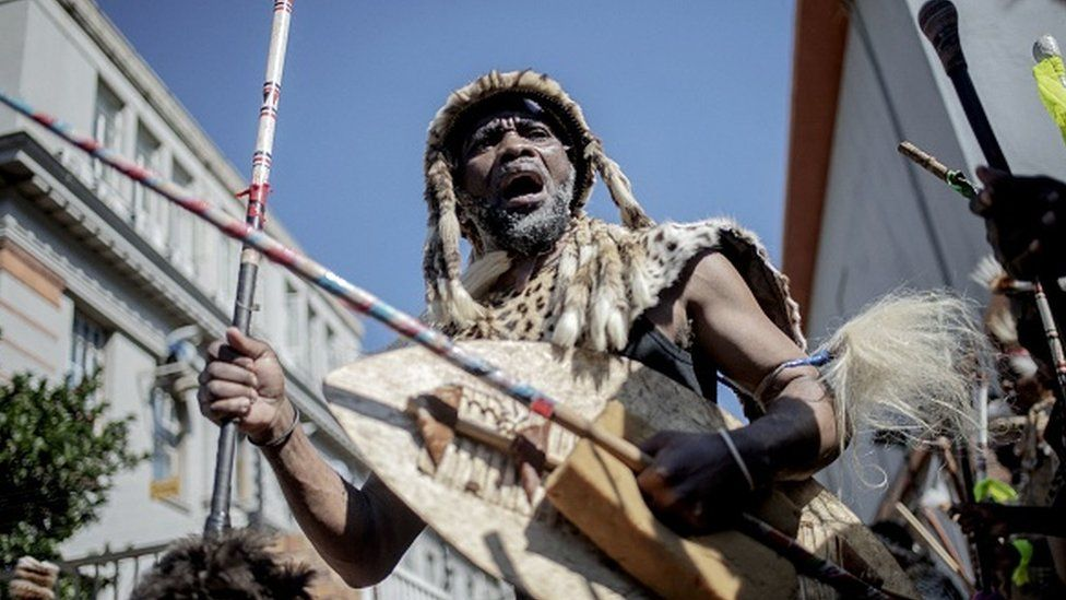 A traditionally dressed Zulu man dances during a gathering in front of a morgue in Johannesburg