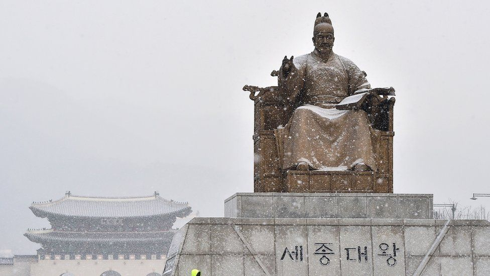 A bronze statue of King Sejong during snowfall in Seoul.