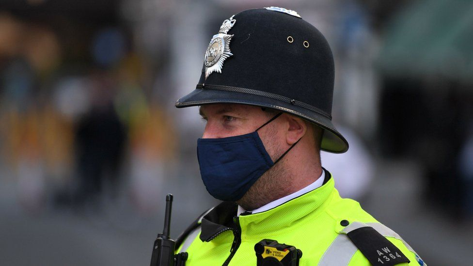 A police officer wearing a protective face covering patrols in Soho in London