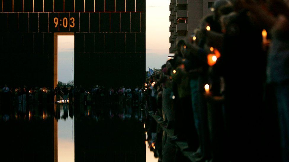 A 09:03 archway and pool lined with people remembering the attack, with candles