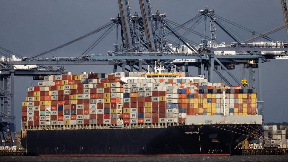 A container ship berthing, stacked high with cargo