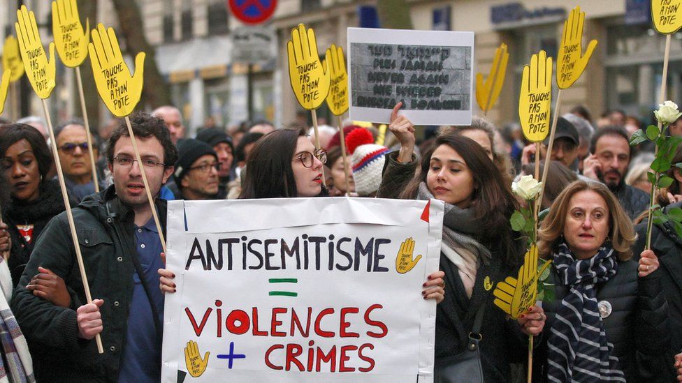 Demonstrators hold signs against anti-Semitism during a silent march in Paris on March 28, 2018, in memory of Mireille Knoll, an 85-year-old Jewish woman murdered in her home in what police believe was an anti-Semitic attack.