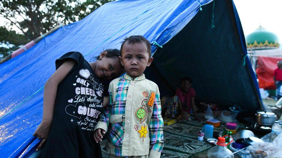Children pose in front of a tent on a field of a mosque where they took refuge in Palu