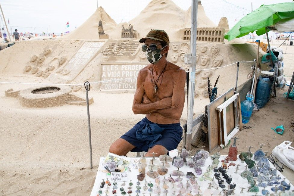 A street vendor selling figurines on the beach