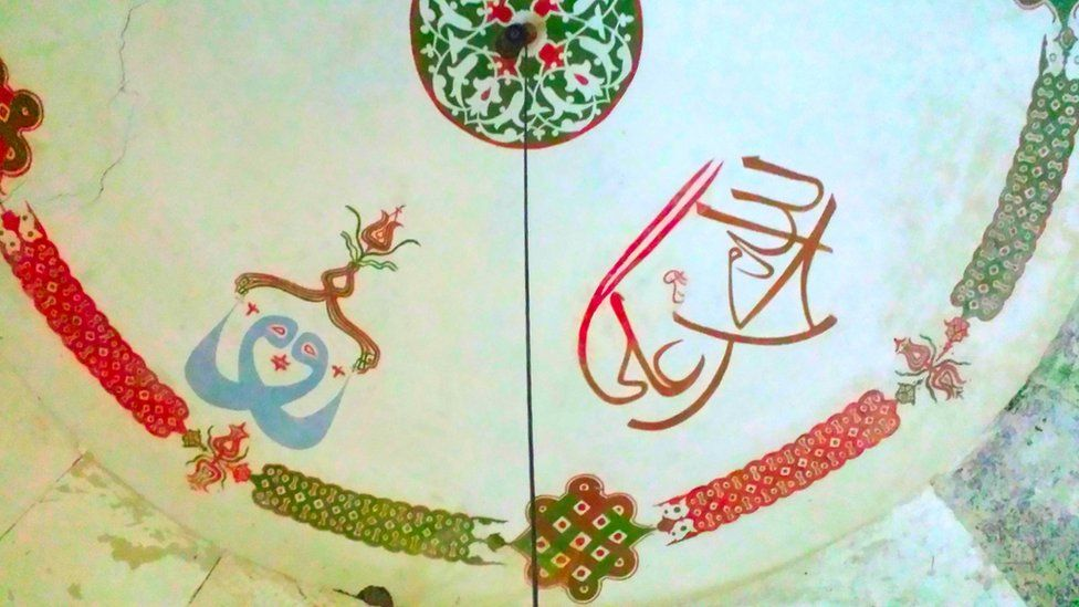 Inscriptions on the ceiling of Demir Baba Tekke, an Alevi mausoleum in north-eastern Bulgaria. The right side has the names Allah, Muhammad and Ali written in legible, simple Arabic. The left side shows a blue mystical pattern within which all three names have been interlocked.