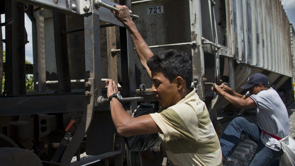 Central American migrants get on the so-called La Bestia (The Beast) cargo train, in an attempt to reach the US border, in Apizaco, Tlaxcala state, Mexico on July 22, 2014