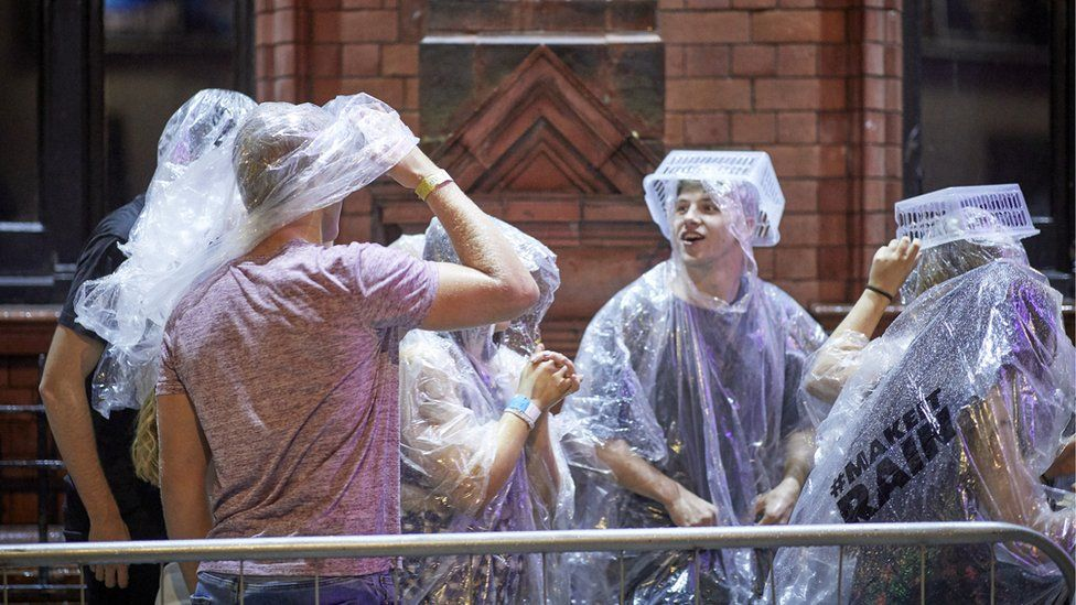 A young crowd shield themselves with plastic ponchos and baskets, in a creative solution to a rainy evening