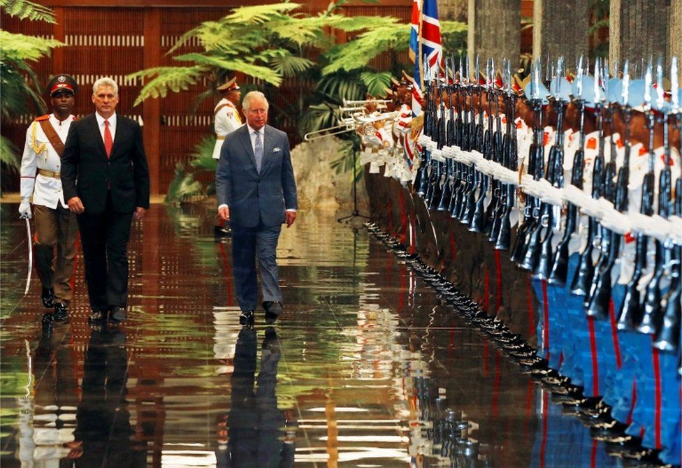 President Miguel Diaz-Canel welcomes Prince Charles walk past the guards at the Palace of the Revolution