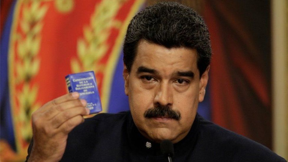 Venezuela's President Nicolas Maduro holds up a book of the country's constitution during a news conference at Miraflores Palace in Caracas, Venezuela August 22, 2017.