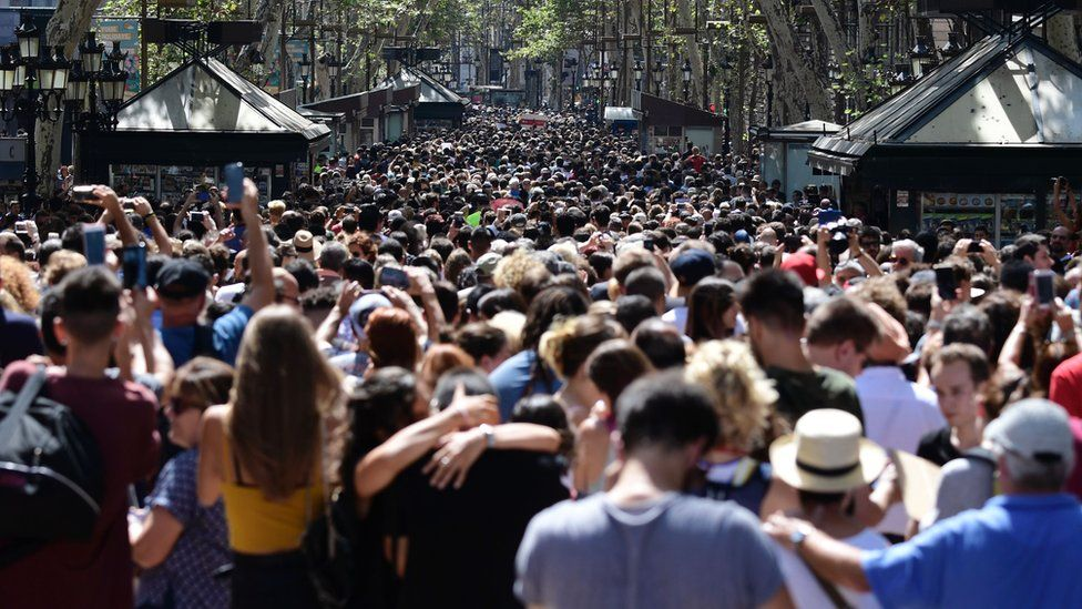 Crowds of people fill Las Ramblas to observe a minutes silence.