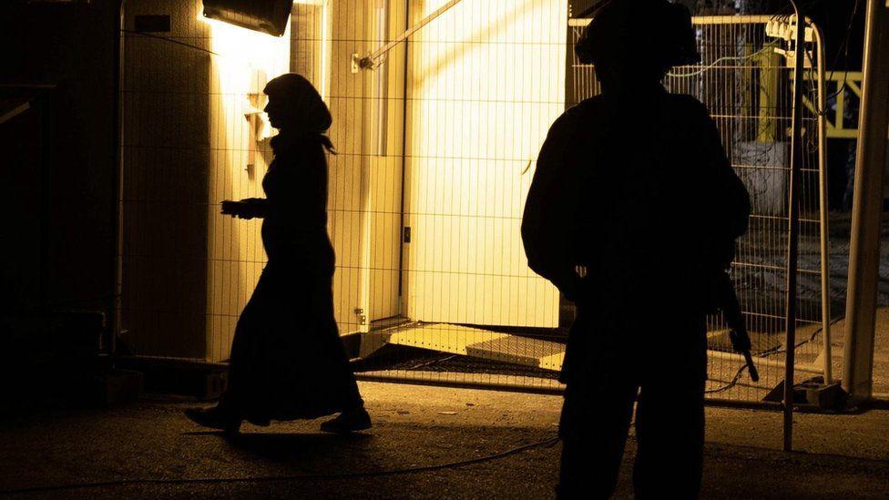 A woman walks past an Israeli soldier