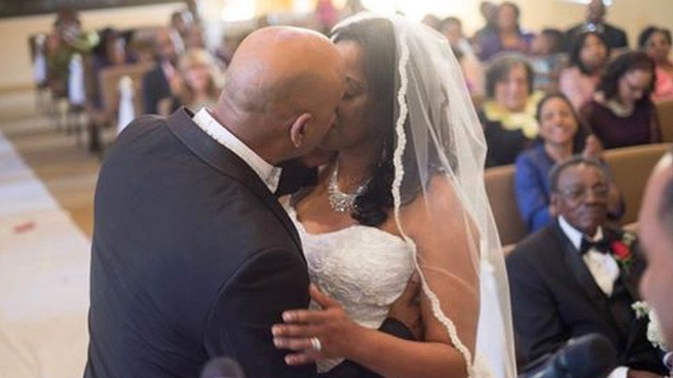Cedric Anderson (L) kisses his wife Karen Smith (R) at their wedding on 28 January.