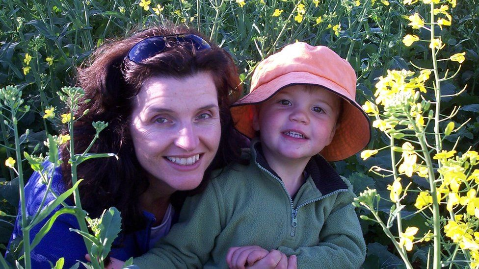 Caroline Welsh and her young son, Angus, on a farm surrounded by yellow crop
