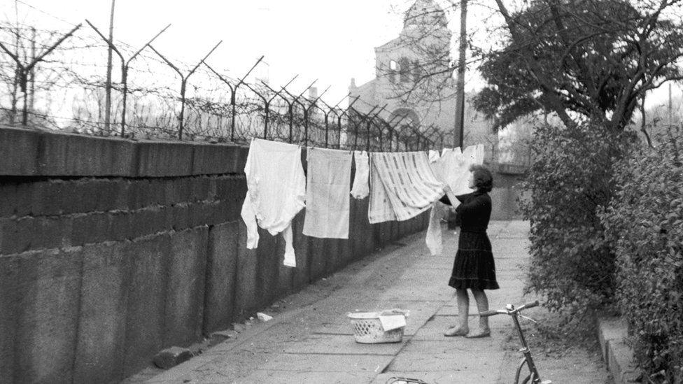 A woman hangs washing on the Berlin Wall