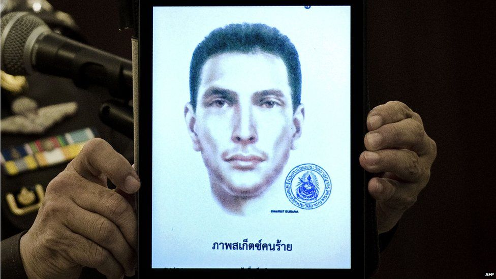 Thailand's national police spokesman Lt Gen Prawut Thavornsiri holds a tablet displaying a picture of an unnamed foreign man wanted by the police at the police headquarters in central Bangkok on Tuesday