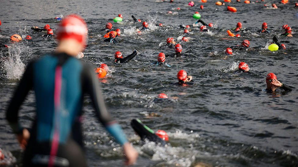 Swimmers participate in an open water swimming event at the Serpentine in Hyde Park, London