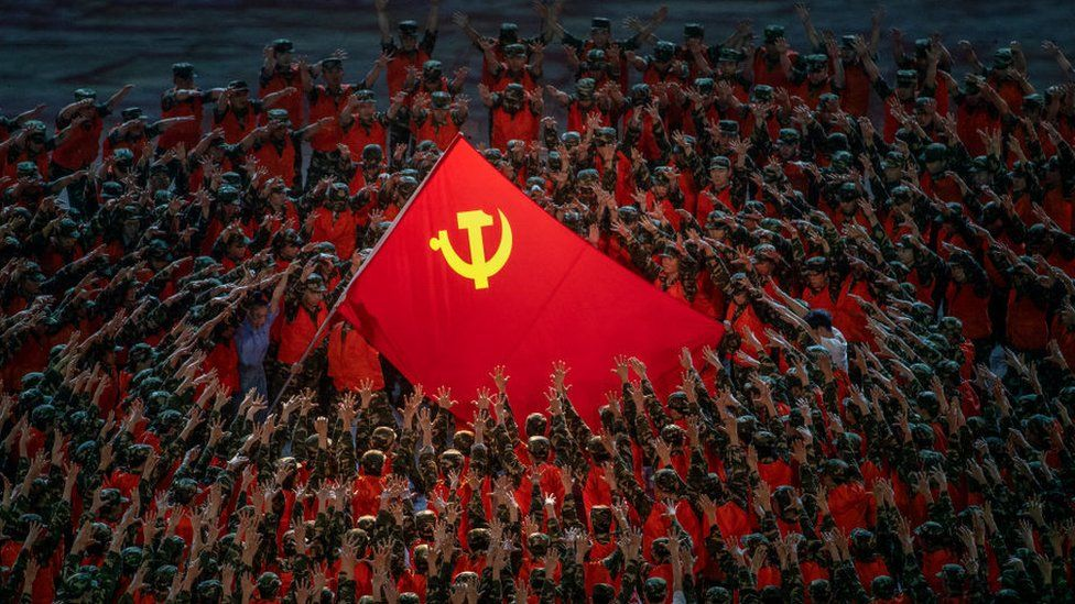 Performers in the costume of emergency workers surround a large Communist Party flag during a mass gala marking the 100th anniversary of the Communist Party on June 28, 2021.