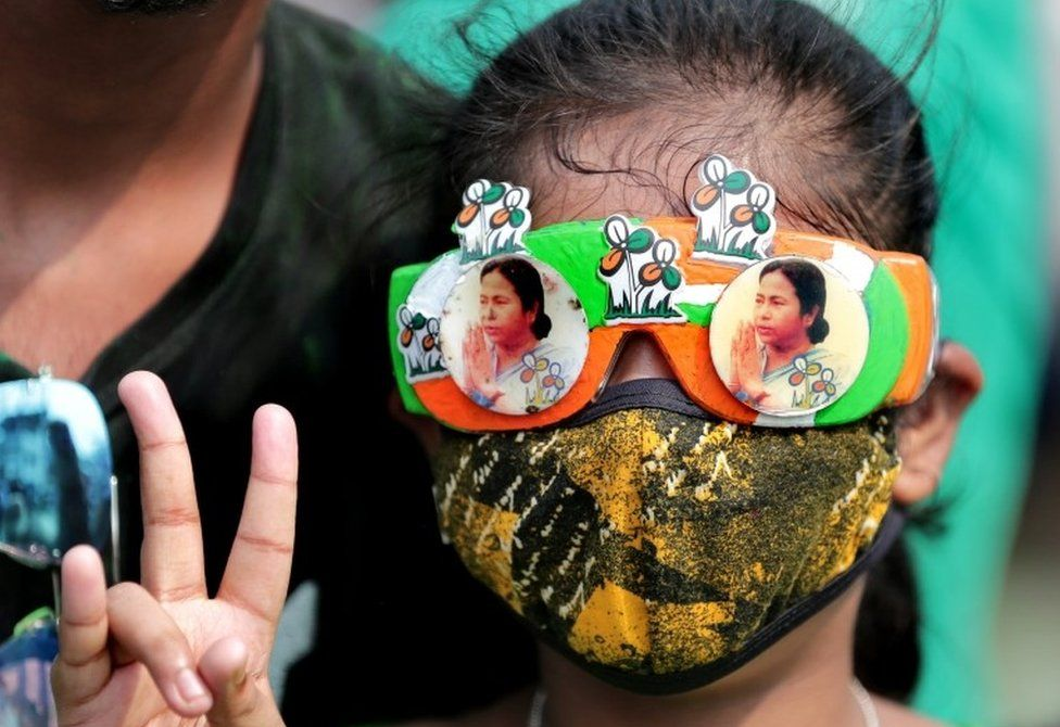 A Trinamool Congress party (TMC) supporter wears glasses with pictures of party supreemo Mamata Bannerjee and shows victory sign as they celebrate after winning an absolute majority in the West Bengal Assembly Election in Kolkata, India, 02 May 2021