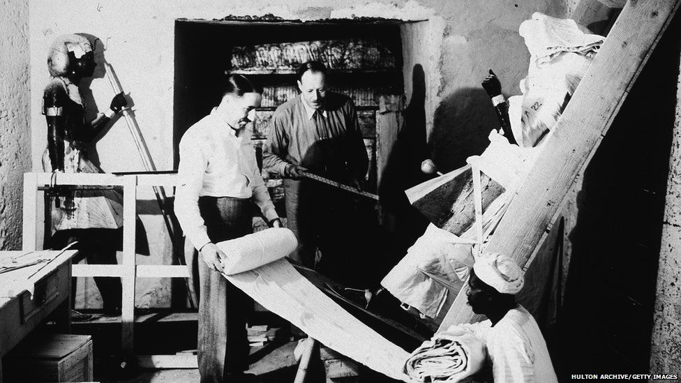 British archaeologists Howard Carter (1874 - 1939) (left) and Arthur Callender (died 1937) carry out the systematic removal of objects from the antechamber of the tomb of Pharaoh Tutankhamen, better known as King Tut, with the assistance of an Egyptian laborer, Valley of the Kings, Thebes, Egypt, 1923
