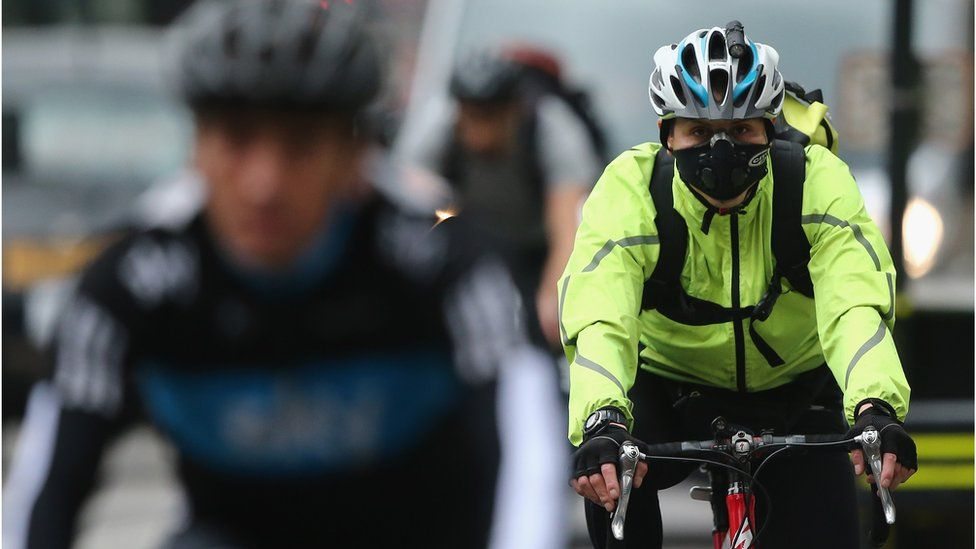 A woman wearing a face mask cycles through Westminster
