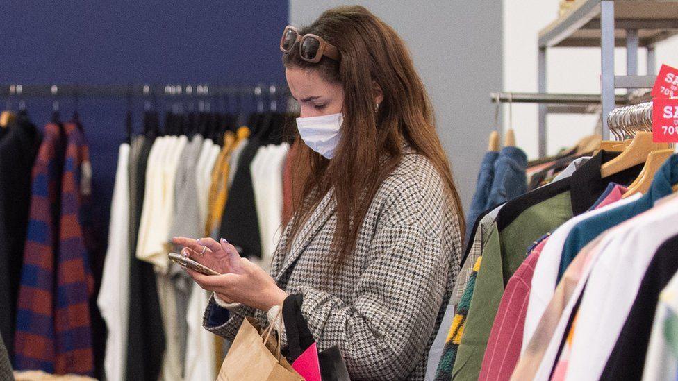A woman checks her phone while shopping