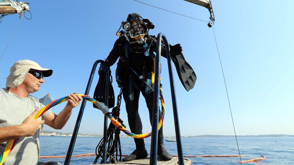 A diver in full gear, about to enter the sea from a boat