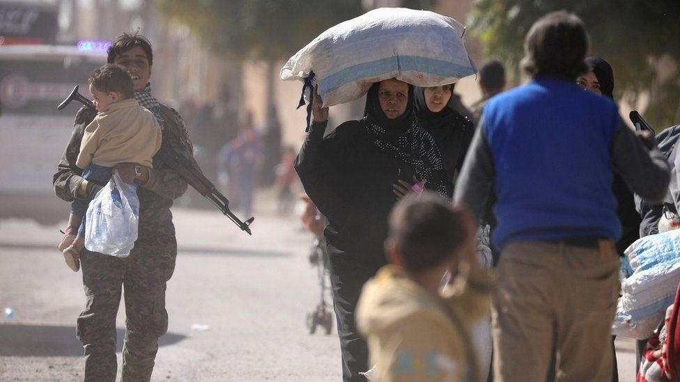 A woman holds her belongings as she flees Raqqa, Syria (16 October 2017)
