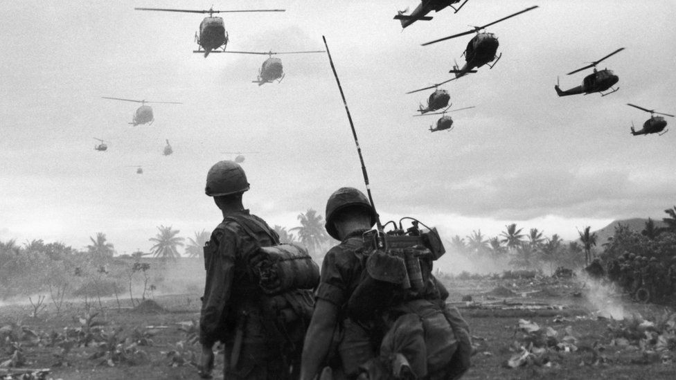 US combat helicopters fly over two American soldiers on an isolated landing zone during Operation Pershing, on the Bong Son Plain and An Lao Valley in South Vietnam, during the Vietnam War.