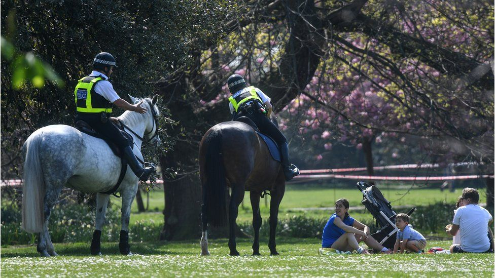 Police on horses speaking to a family