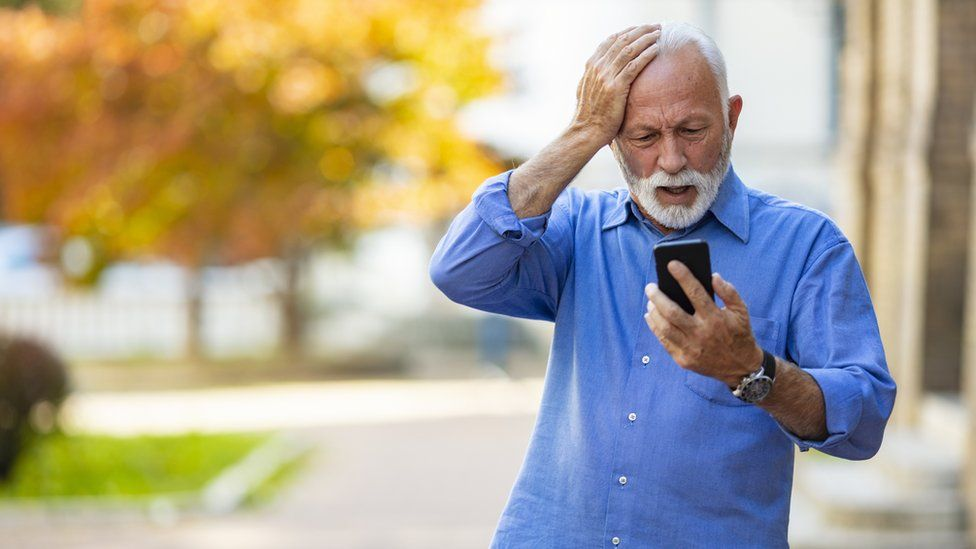 Old man surprised by phone