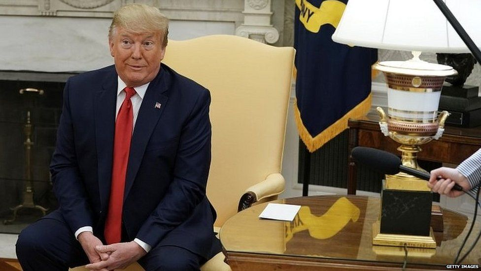 Donald Trump sitting in the Oval Office