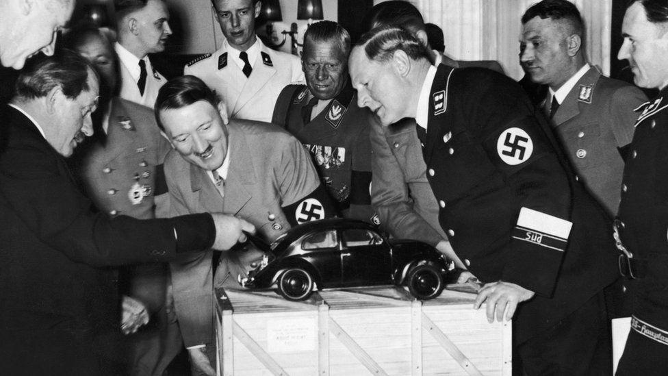 Adolf Hitler looks at a model of the Volkswagen car. He is with the designer Ferdinand Porsche (left)