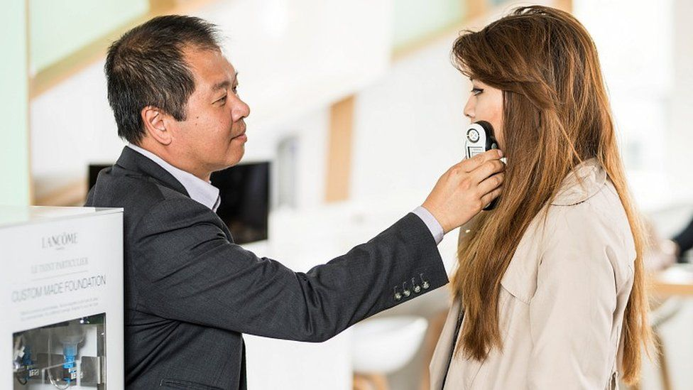 Man scanning woman's face with hand-held scanner