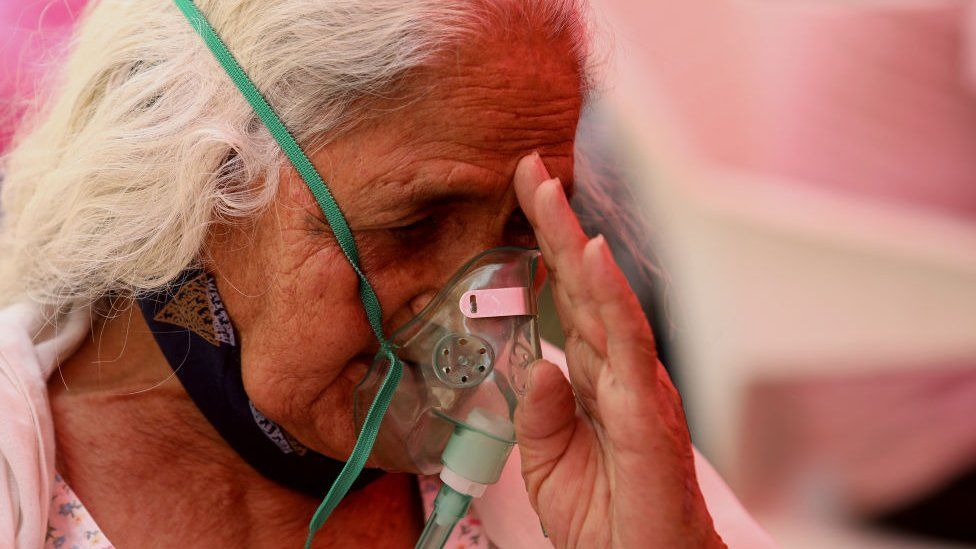 A Covid-19 patient who is suffering from breathing difficulty breaths with the help of oxygen mask outside Gurudwara.