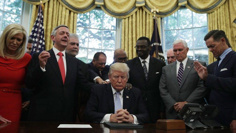 .S. President Donald Trump, Vice President Mike Pence and faith leaders say a prayer during the signing of a proclamation in the Oval Office of the White House September 1, 2017 in Washington, DC