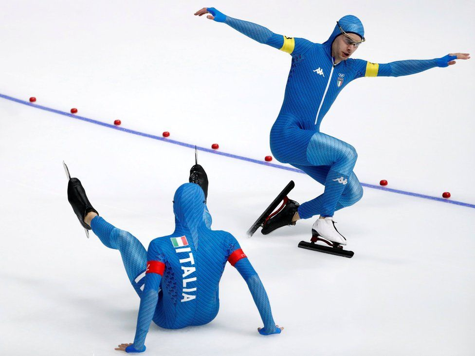 Nicola Tumolero and Riccardo Bugari seen on the ice, one with arms outstretched, the other sitting on the ice