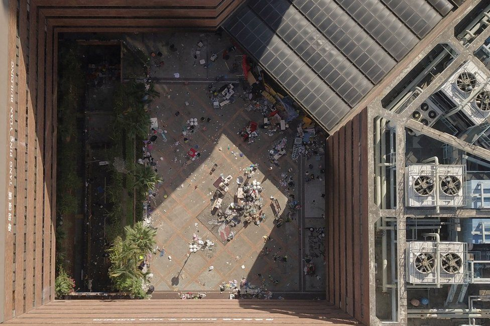 An aerial view shows the main entrance (top R) to the campus and debris leftover from protesters who barricaded themselves inside, at the Hong Kong Polytechnic University in the Hung Hom district in Hong Kong on 22 November 2019.