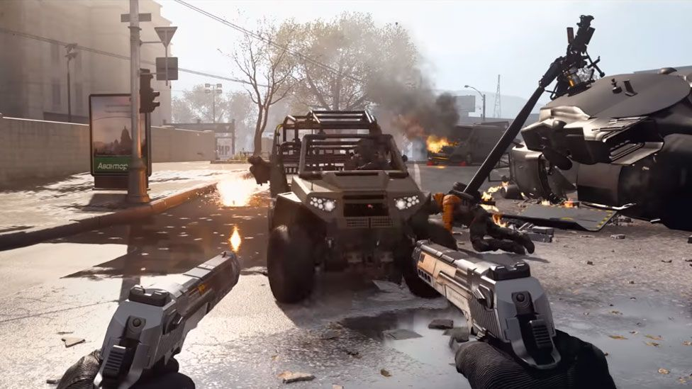 A first-person view shows the burning vehicles on a street, with the player's hands visible in-frame holding two pistols