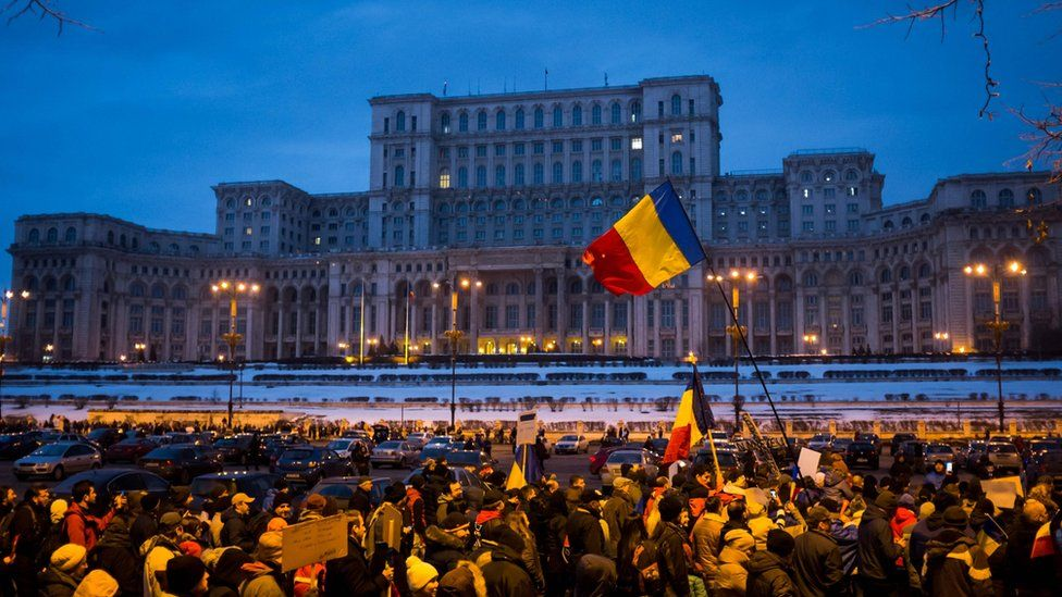 """People march in front of the Romanian parliament during a rally against the government""""s contentious corruption decree on February 4, 2017, in Bucharest, Romania"""