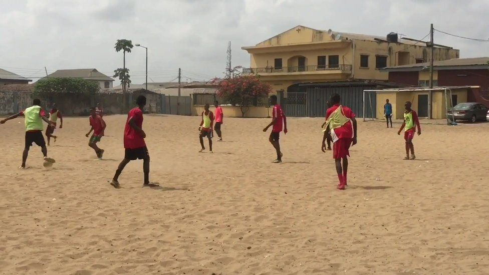 Boys playing football in an open space