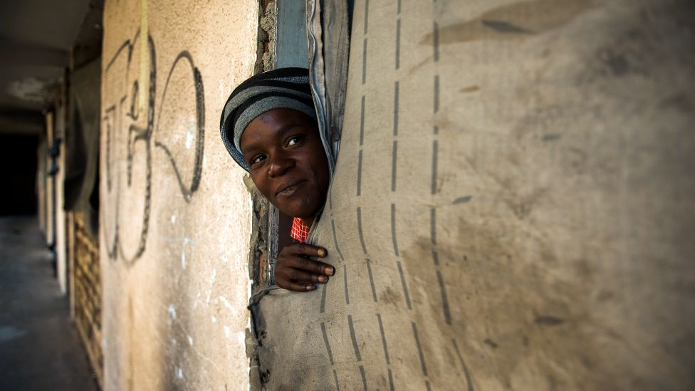 An unidentified woman peeks out of her room. With the doors and door frames removed, a fabric sheet serves as a makeshift door in the derelict San Jose building in Johannesburg, South Africa