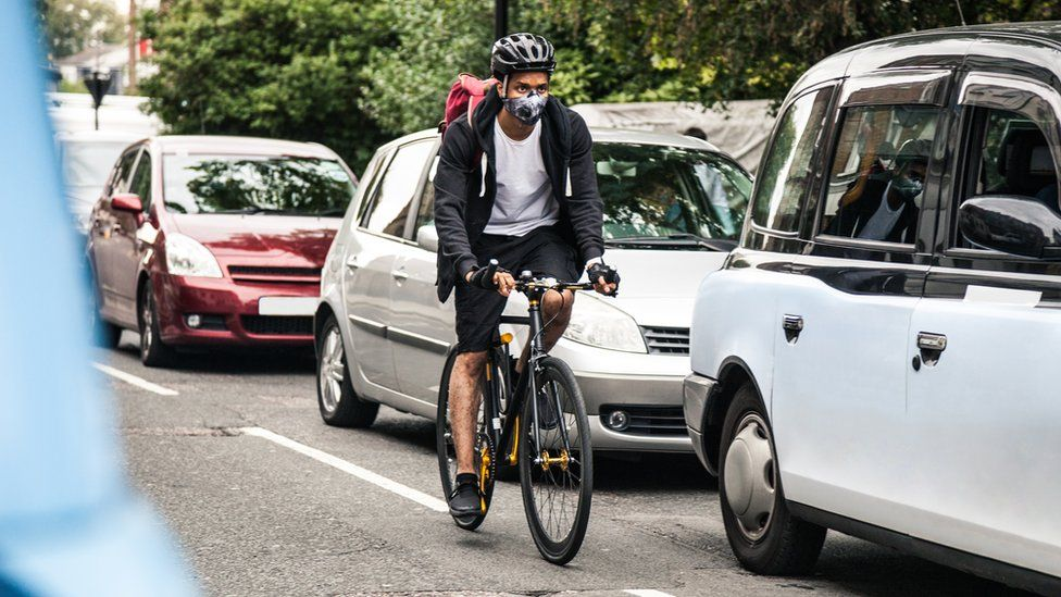 Cyclist commuter cycling through central London traffic while wearing a pollution mask.
