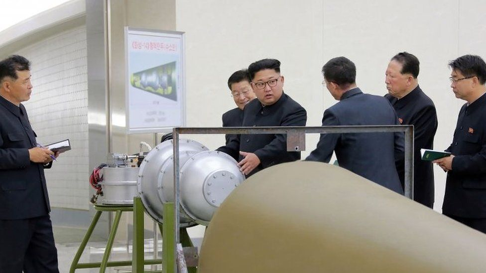 North Korean leader Kim Jong-Un (C) looking at a metal casing with two bulges at an undisclosed location