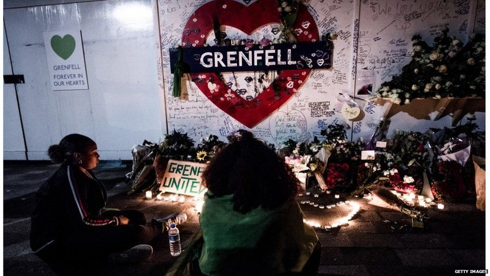 A woman seen standing in front of the flowers memorial at the foot of the Grenfell Tower