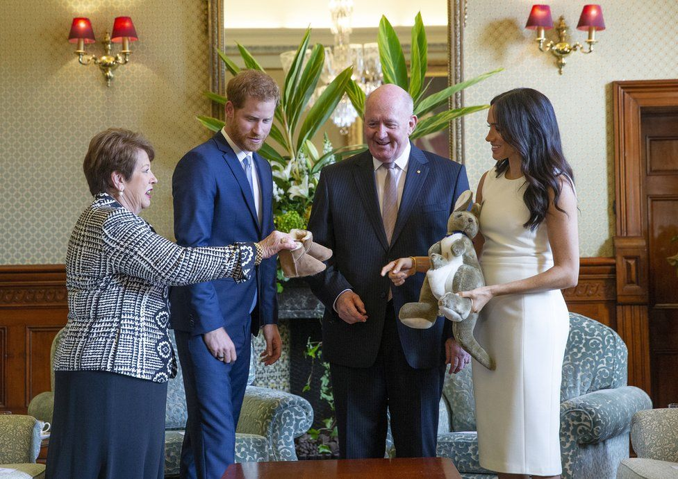 """Australian Governor-General Sir Peter Cosgrove (2-R) and his wife Lady Cosgrove (L) present a toy kangaroo and a pair of small ugg boots to Britain""""s Prince Harry (2-L), the Duke of Sussex, and his wife Meghan (R), the Duchess of Sussex, during an event at Admiralty House in Sydney, Australia, 16 October 2018"""