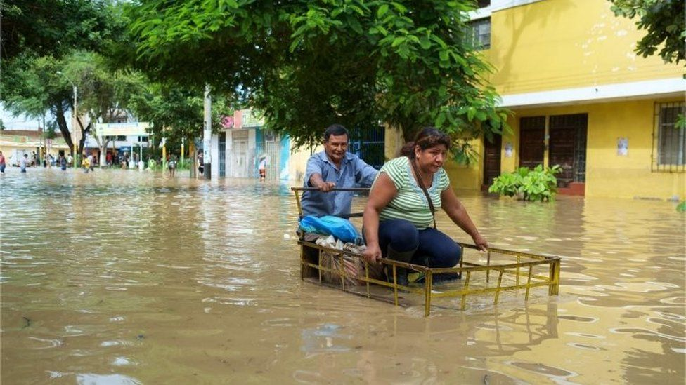 Two people try to advance along a street flooded by the Piura river in Piura, Peru, 27 March 2017.