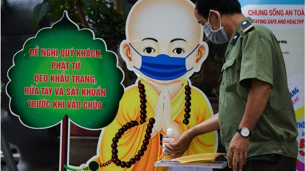A local security officer disinfects his hands in Quan Su pagoda in front of a monk illustration wearing a face mask