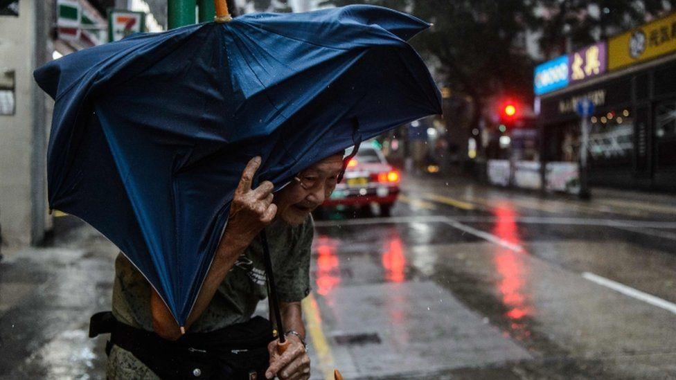 An elderly man man struggles with an umbrella in a Hong Kong city street