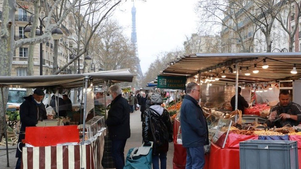 People shop at an open air market in Paris on March 21, 2020